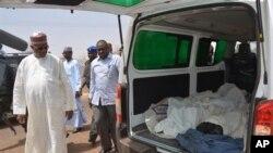 Ibrahim Gaidam, Gubernur negara bagian Yobe, Nigeria menginspeksi tubuh siswa di sebuah ambulan di Damaturu, Nigeria. Militan Islam menewaskan 29 siswa dalam sebuah serangan.