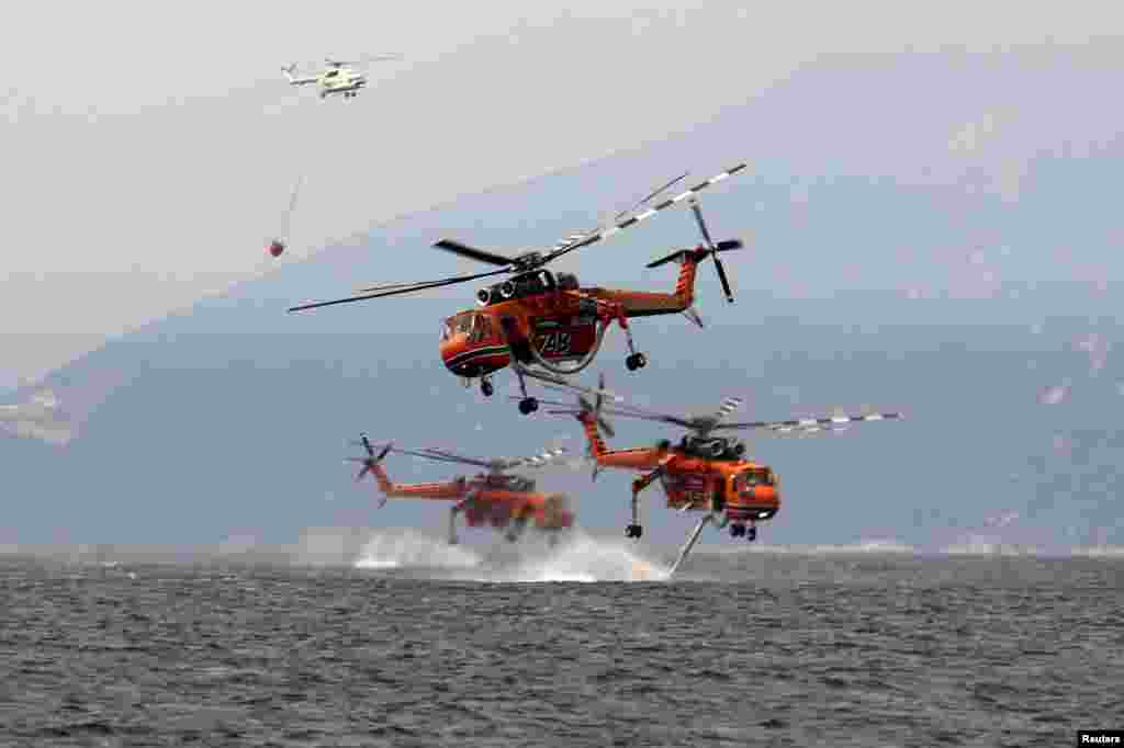 Firefighting helicopters are filled with water off the beach of the village of Pefki, on the island of Evia, Greece, Aug. 10, 2021.