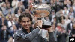 Petenis Spanyol, Rafael Nadal memegang trophy juara Perancis Terbuka untuk yang ke-7 kalinya setelah mengalahkan Novak Djokovic (11/6).