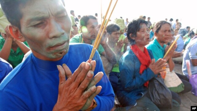 Cambodian villagers affected by the loss of land in Prey Lang forest in the north of the country pray at a Buddhist shrine in central Phnom Penh, August 18, 2011. Later, most were briefly detained after they distributed leaflets in the capital, but they w