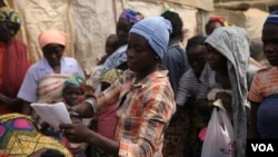 Blessing John, who escaped from Boko Haram, hands out used clothes to internally displaced people at the Sabon Kuchigora refugee settlement on the outskirts of Abuja, Dec. 17. (Chris Stein/VOA)