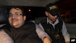 Mexico's former Veracruz state Gov. Javier Duarte, left, is escorted by an agent of the local Interpol office inside a police car as they arrive at Guatemala City, early Sunday, April 16, 2017.