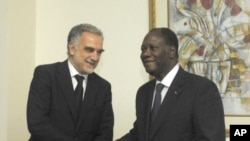 International Criminal Court's chief prosecutor Luis Moreno-Ocampo, left, is greeted by Ivory Coast President Alassane Ouattara in Abidjan, Ivory Coast, October 15, 2011.