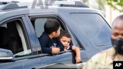 Josué Moreno y su hermano Javier esperan a que miembros de la Guardia Nacional de Washington entreguen a su familia una ración de comida. [Archivo]