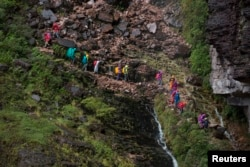 Tourists walk down from the top of Mount Roraima, near Venezuela's border with Brazil, Jan. 18, 2015.