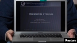 FILE - A cyber warfare expert who is chief technology officer of the U.S. Cyber Consequences Unit, a non-profit group that studies the impact of cyber threats, holds a notebook computer while posing for a portrait.