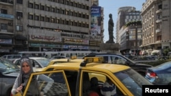 FILE - A woman exits a taxi during rush hour in central Damascus, Syria, Sept. 16, 2018.