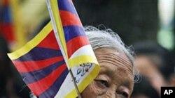 4月24日一名藏人举着西藏旗帜参加在印度达兰萨拉举行的抗议