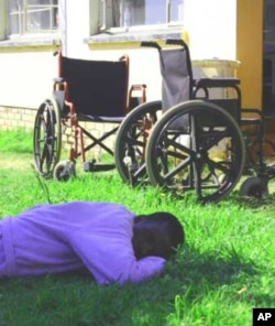 A patient who's become disabled because of TB sleeps on the grass outside a ward at Zithulele Hospital