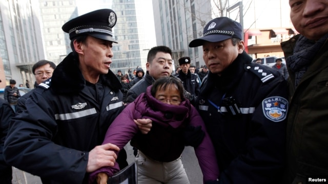 Liu Chunxia, a supporter of Xu Zhiyong, one of China's most prominent rights advocates, is detained by policemen while she gathers with other supporters nearby a court where Xu's trial is being held in Beijing, Jan. 22, 2014.