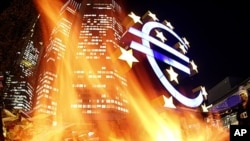 In this photo taken with a fisheye lens, flames from a fire set alight in a container by activists of the Frankfurt Occupy movement are seen in front of the European Central Bank and a sculpture of the euro symbol in Frankfurt, Germany, November 21, 2011