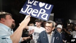 FILE - Scott Paterno (L) looks on as students greet his father, Penn State football coach Joe Paterno, as he arrives at his home in State College, Pa., Nov. 8, 2011.