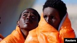 Des migrants attendent en ligne dans un bateau au port de Pozzallo, en Italie, le 29 mars 2016.