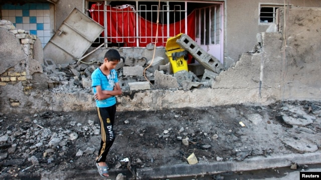 A youth stands at the site of a car bomb attack in Baghdad, a day after the bombing, Aug. 29, 2013.