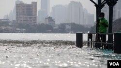 Seorang warga Thailand berdiri di dekat jembatan yang tergenang air di sungai Chao Praya, Bangkok (14/10).