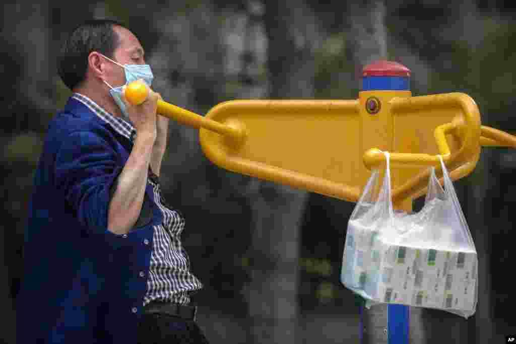 این مرد در شهر پکن بعد از خرید روزانه از امکانات یک پارک برای ورزش استفاده میکند. چین میگوید کل کشور اینک در پایینترین خطر ابتلا به کرونا قرار دارد. آمار رسمی چین، روسیه و ایران قابل راستی آزمایی توسط کارشناسان مستقل نیست و نمیتواند معتبر و نهایی تلقی شود.