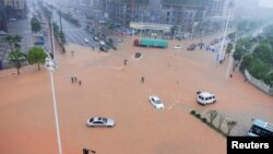湖南长沙,大路积水,行人和车辆冒雨过马路(2017年7月1日)