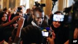 ທ້າວ Lassana Bathily (ກາງ) ອົບພະຍົບຄົນມາລີ ຜູ້ທີ່ຊ່ວຍຊີວິດ ບັນດາລູກຄ້າຊາວຢິວ ເມື່ອອາທິດແລ້ວນີ້ ໂດຍການຊຸກເຊື່ອງ ພວກເຂົາເຈົ້າໄວ້ຢູ່ຊັ້ນລຸ່ມຂອງຮ້ານຄ້າຂາຍ ອາຫານການກິນຂອງຊາວຢິວ ໂອ້ລົມກັບພວກເດັກນ້ອຍ ຢູ່ທີ່ສາລາເມືອງຂອງນະຄອນ ຫລວງປາຣີ ປະເທດຝຣັ່ງ, ວັນທີ 16 ມັງກອນ 2015.
