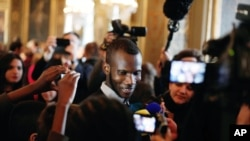 Lassana Bathily, tengah, imigran Mali dan seorang pekerja toko kelontong halal di Paris yang diserang seorang pria bersenjata yang menyelamatkan beberapa orang Yahudi yang sedang berbelanja minggu lalu, berbicara dengan anak-anak di Balai Kota Paris, Perancis, 16 Januari 2015.