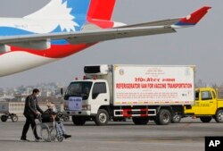 A van stands parked waiting to transport AstraZeneca/Oxford University vaccines, manufactured under license by Serum Institute of India, at Tribhuwan International Airport in Kathmandu, Nepal, Thursday, Jan. 21, 2021.