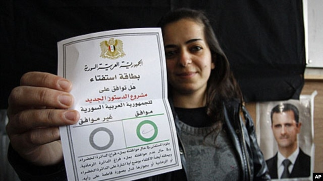 A Syrian woman displays her ballot at a polling station during a referendum on the new constitution, in Damascus, Syria, Sunday, February 26, 2012.