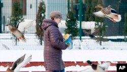 Une femme nourrit dans des canards en plein hiver dans un pars à Varsovie, Pologne, 20 janvier 2016.