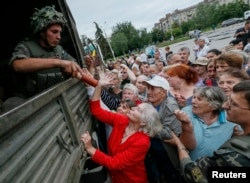 People receive food aid from Ukrainian soldiers in Slovyansk, Ukraine, July 6, 2014.