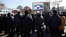 29일 평양 기차역에서 북한 주민들이 화성-15 미사일 발사에 관한 정부 성명을 대형스크린으로 시청하고 있다.