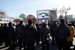 지난달 29일 평양 기차역에서 북한 주민들이 화성-15 미사일 발사에 관한 정부 성명을 대형스크린으로 시청하고 있다.