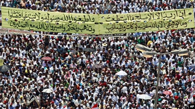Protesters gather with a banner with a Koranic verse in Tahrir square in Cairo, July 29, 2011