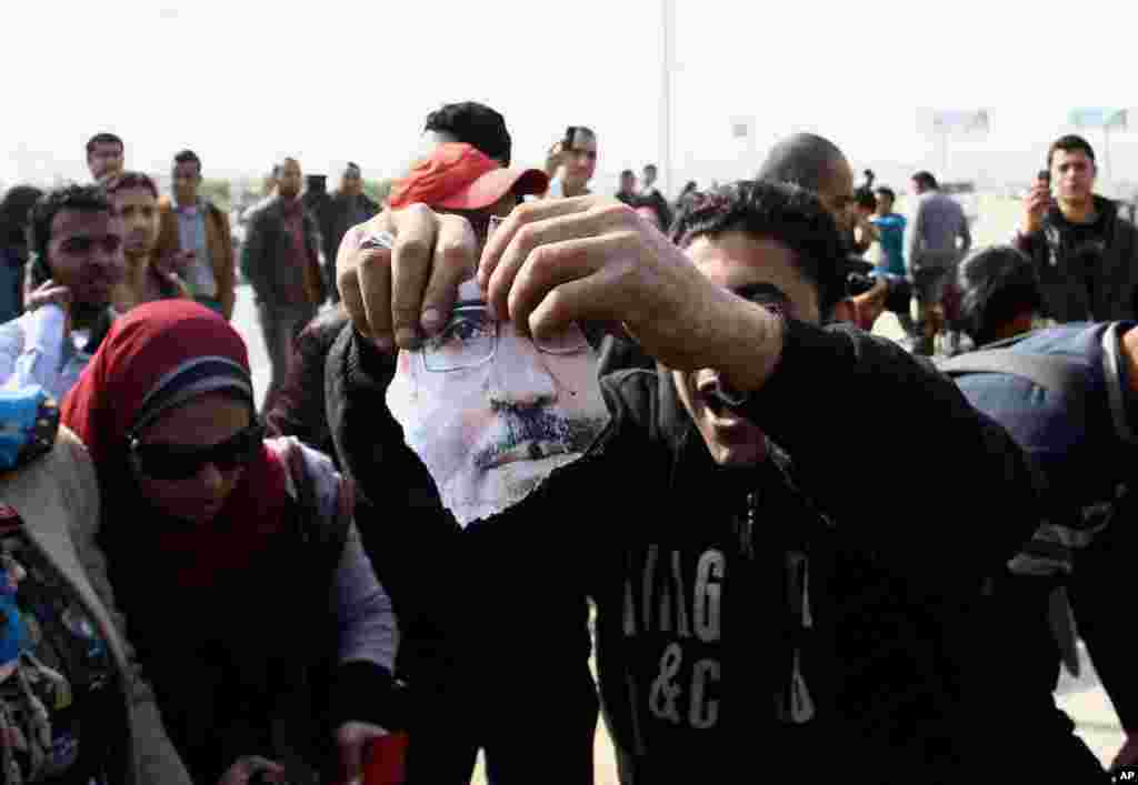 A man holds a part of a torn poster showing Egypt's ousted President Mohamed Morsi during clashes in Cairo, Jan. 8, 2014.