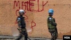 Sòlda mentyen lapè Nasyonzini ka p pase devan yon mi nan Pétion-Ville ki gen non--graffiti-- Michel Martélly, jou eleksyon 28 novanm 2010 la