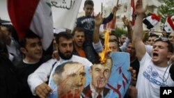 Syrian protesters shout slogans as they burn a poster of Syrian President Bashar Assad, left, and his father Hafez Assad during a demonstration in front of the Syrian embassy, in Nicosia, Cyprus, April 22, 2011.