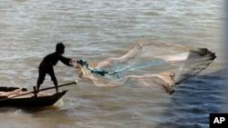一位漁民在金邊的湄公河上撒網。(資料照)