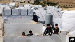 Syrian refugees children climb a concrete wall at a refugee camp in the eastern Lebanese border town of Arsal, Lebanon, Aug. 5, 2019.