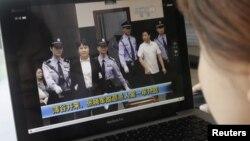 Seorang perempuan sedang mengamati berita yang menampilkan Gu Kailai dalam pengawalan ketat sedang memasuki ruang sidang pengadilan kota Hefei (9/8).
