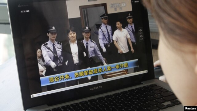 A woman watches a CCTV video showing Gu Kailai being escorted into the court room at Hefei Intermediate People's Court, August 9, 2012.