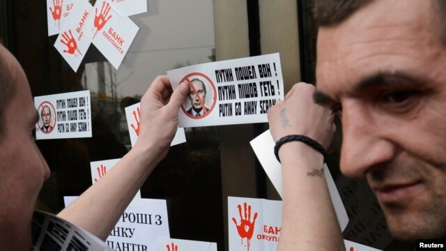 A member of a Ukrainian self-defense unit attaches stickers during a rally outside an office of Alfa bank in Kyiv, March 26, 2014. Participants were demanding that people stop using the services of Alfa bank, which has Russian origin, according to organizers.