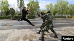 FILE - Border police take part in an anti-terrorism drill near Baketu border in Tacheng, Xinjiang Uighur Autonomous Region, China, April 28, 2016.