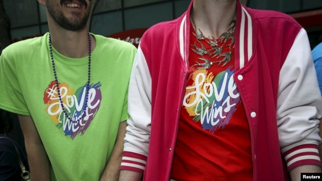 "FILE - Two men wearing shirts with ""#LoveWins"" written on them watch the 2015 San Francisco gay pride parade."