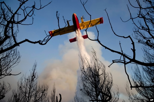 FILE - A firefighting plane drops its load during a forest fire near the village of Metohi north of Athens, Aug. 14, 2017.