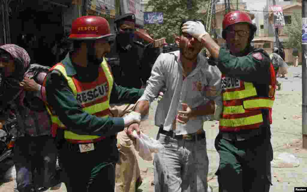Rescue workers assist an injured supporter of Tahir-ul Qadri of the political party Pakistan Awami Tehreek, during a protest in Lahore, June 17, 2014.