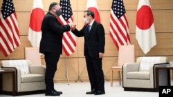 Japan's Prime Minister Yoshihide Suga, right, and U.S. Secretary of State Mike Pompeo pose as they attend a meeting at the prime minister's office in Tokyo Tuesday, Oct. 6, 2020, ahead of the four Indo-Pacific nations' foreign ministers meeting. …
