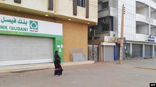 A woman walks past two closed banks in a deserted street in Sudan's capital Khartoum, Sudan, June 4, 2019.