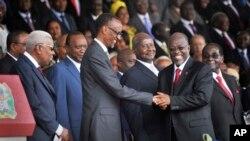 Presiden Tanzania baru John Magufuli, kanan tengah, menerima ucapan selamat dari Presiden Rwanda Paul Kagame, kiri tengah saat upacara pelantikan. (AP Photo/Khalfan Said)