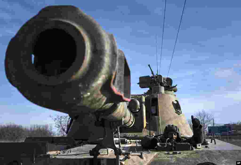 A Ukrainian soldier rides a self-propelled artillery piece near Artemivsk, eastern Ukraine, Feb. 23, 2015.
