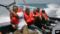 Cuban migrants picked up earlier on Puerto Rico's remote Mona Island sit on the deck of a U.S. Border Patrol boat. Now they are being sent to a processing center on mainland Puerto Rico where they could seek asylum.