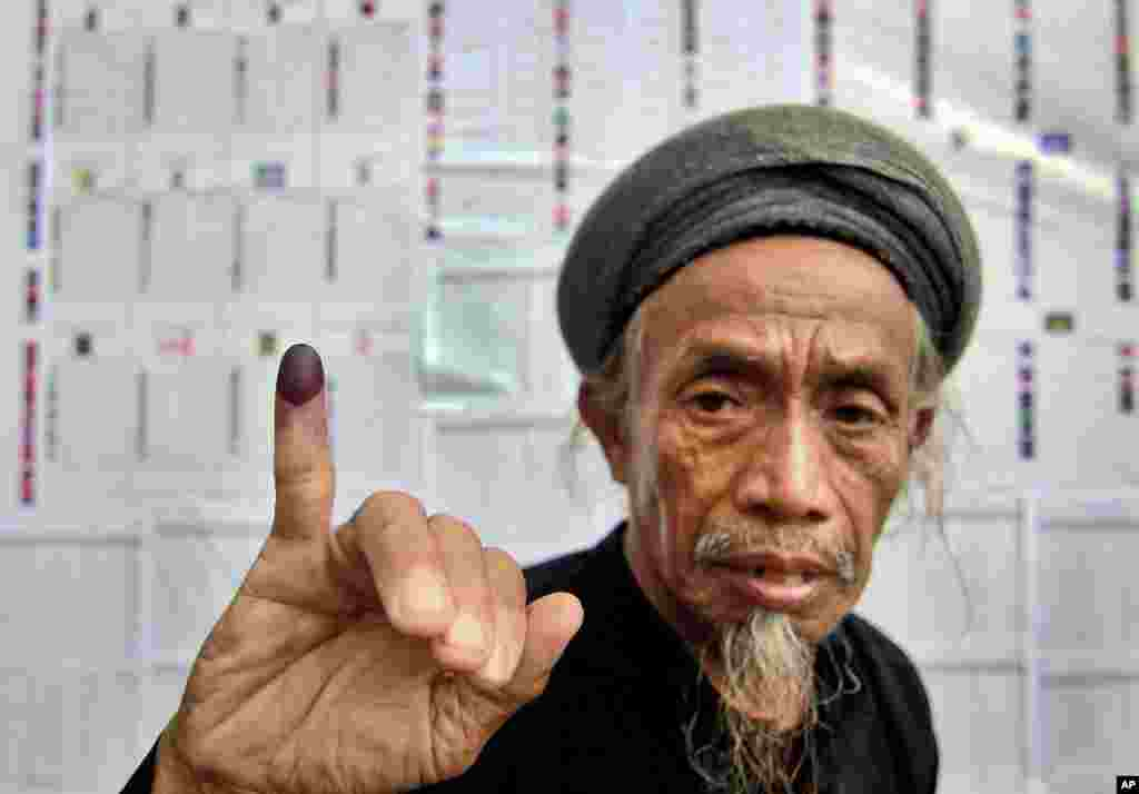 A member of the An-Nadzir Muslim group shows his inked finger after casting his ballot at a polling station during the parliamentary election in Gowa, South Sulawesi, Indonesia, April 9, 2014.