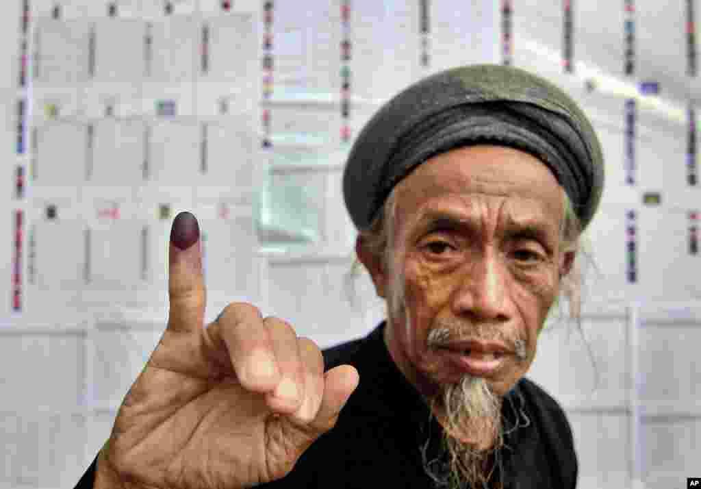 Anggota Muslim An-Nadzir memamerkan jarinya yang sudah ditandai tinta setelah memberikan suaranya di TPS di Gowa, Sulawesi Selatan, Indonesia, 9 April 2014.