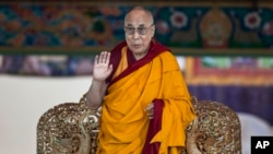 FILE - Tibetan spiritual leader the Dalai Lama gestures to devotees before he starts teaching on the fifth day of Kalachakra near Leh, India.